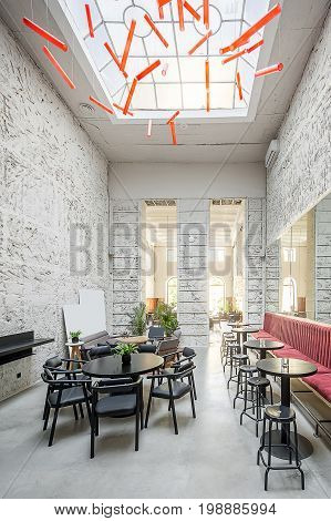 Restaurant with light textured walls and a large window on the ceiling. There are red and gray sofas, round wooden tables, stools and chairs, plants, hanging red lamps, mirrors, doorway to next hall.