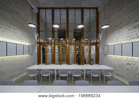 Illuminated hall in the cafe with shabby light walls and gray floor. There are white tables with chairs, frames on the wall, hanging round lamps, large wooden partition with windows and glass doors.