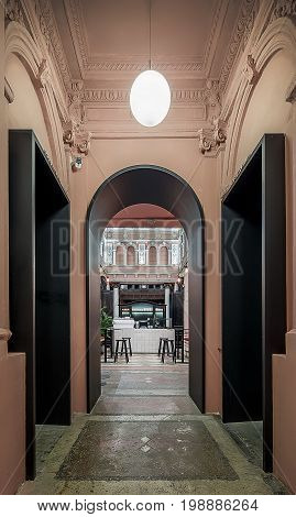 Arch black doorway to the hall in a restaurant with walls with stucco molding. There is a tiled rack , wooden sideboard, tables with stools, textured floor, hanging luminous lamps. Indoors. Vertical.