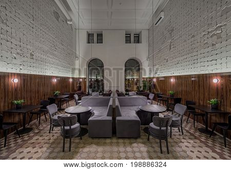 Restaurant in a loft style with shabby light walls with textured wooden panels and tiled floor. There are luminous lamps, multicolored sofas, different tables and chairs, arch windows, plants.