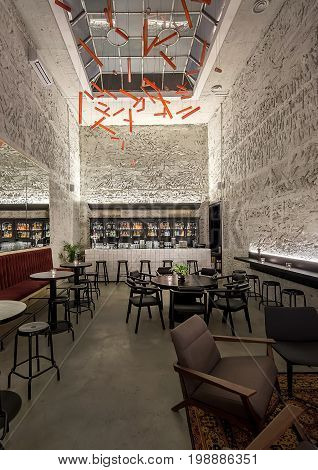Illuminated bar with textured walls and a large window on the ceiling. There are red sofas, black round tables, stools and chairs, plants, tiled bar rack, shelves with bottles, hanging red lamps.