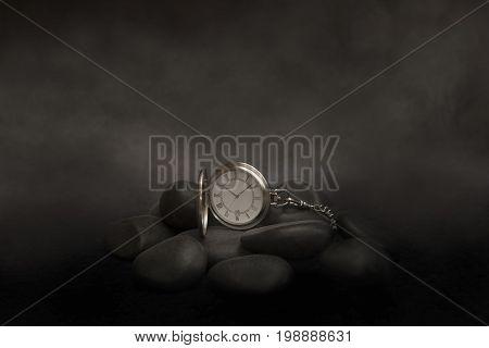 A metal pocket watch sitting on black rocks with a smoky background.