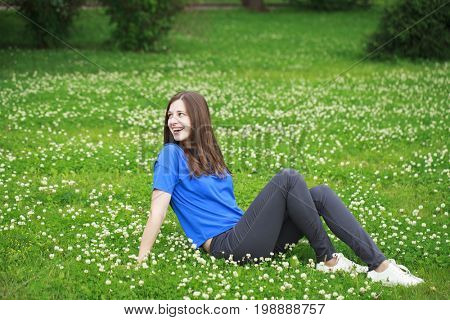 Happy young brunette woman in pants and a blue blouse in the summer park