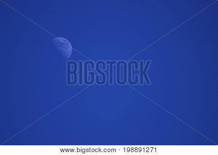 Faded partial moon on a clear blue sky.