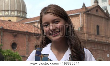 A Young Hispanic and Smiling Teen Girl Near Church
