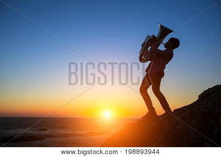 Silhouette of musician play Tuba on sea shore at sunset.