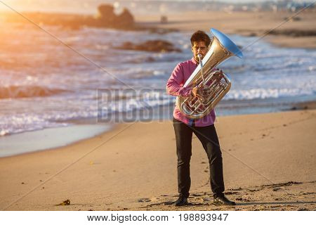 Musician playing the Tuba musical instrument on the sea coast. Romantic.