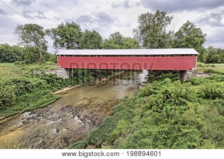 The historic and newly restored Scipio Covered Bridge crosses Sand Creek on a cloudy day in rural Jennings County Indiana.