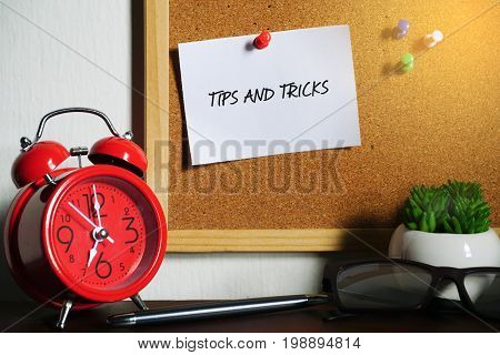 White note written with Tips and Tricks on cork board. Red alarm clock, pen, eye glasses, plant and cork board on white background.