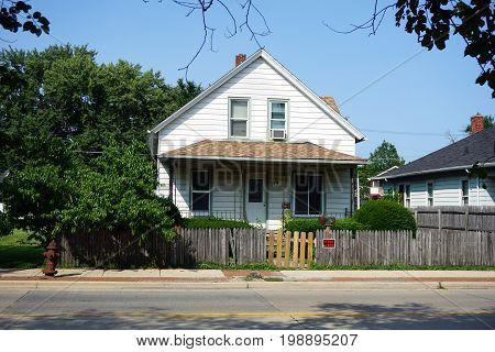 JOLIET, ILLINOIS / UNITED STATES - JULY 17, 2017: A small single family Cape Cod style home, with a picket fence, on Plainfield Road in Joliet.