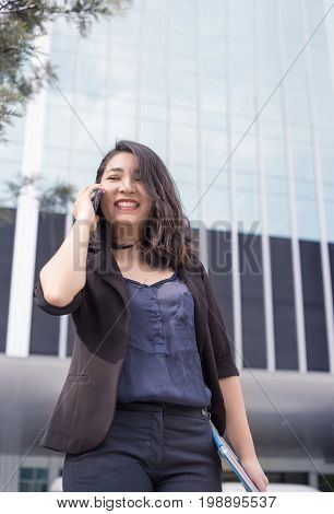 confidence smart asian business lady hold her laptop and talking front of high building in urban location action smile