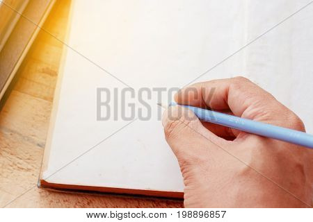 close up male hand with pencil writing something on white paper background (education concept)