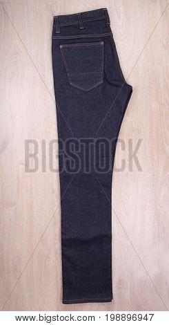 Folded dark blue jeans on wooden background