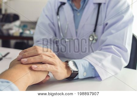 Close up of doctor touching patient hand for encouragement and empathy on the hospital cheering and support patient Bad news medical examination trust and ethics.