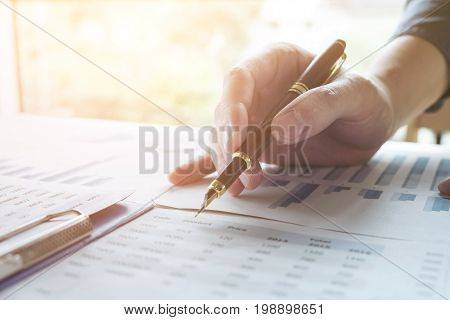 Business man working analyzing data in office Image of confident executive analysis new financial project plan to investment with many documents graph information on wooden desk in living room.
