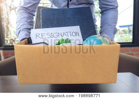 businessman carrying packing up all his personal belongings and files into a brown cardboard box to resignation resign concept.