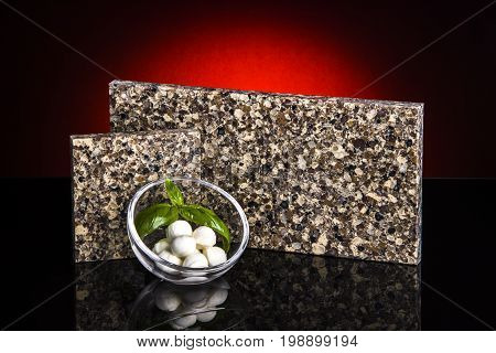 Countertop. Kitchen countertop. Samples of granite countertops with mozzarella. Modern countertops on black table.