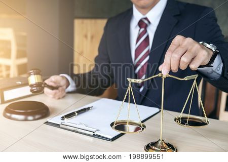 Male lawyer working with gavel and scales of justice note paper report the case on wooden table in office Law and justice concept.
