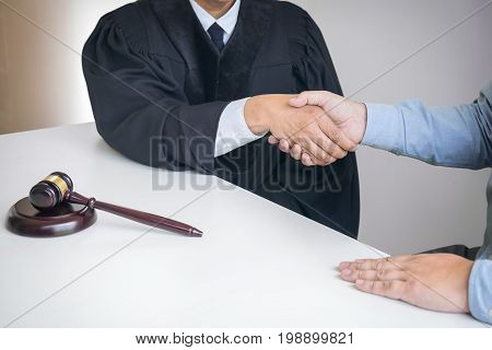 Image of hands Male lawyer or judge and client shaking hands on table after good deal in modern office Near gavel Concept of legal services law legal advice.