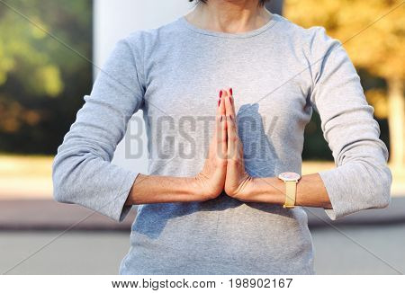 Close Up Of Body Woman Doing Namaste Gesture Outdoors