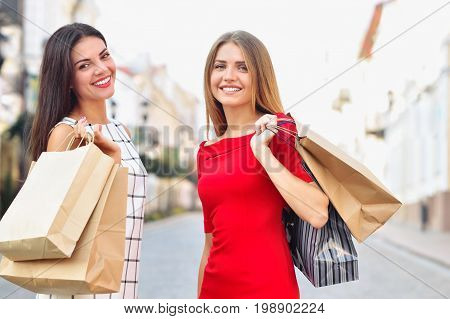 Beautiful Girls With Shopping Bags Are Looking At Camera