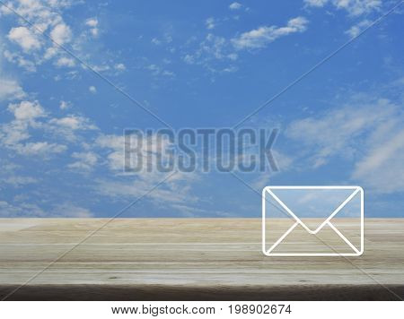 Mail icon on wooden table over blue sky with white clouds Contact us concept