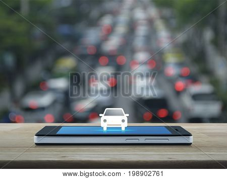 Car flat icon on modern smart phone screen on wooden table over blur of rush hour with cars and road Business transportation service concept