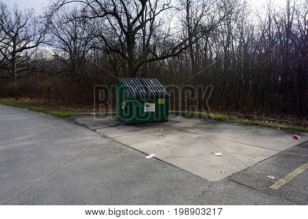 SHOREWOOD, ILLINOIS / UNITED STATES - DECEMBER 6, 2015: A garbage dumpster sits in the corner of a parking lot in the Hammel Woods Forest Preserve.