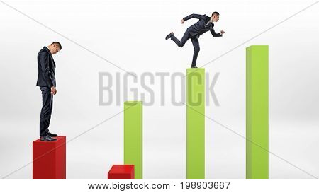 A sad businessman standing on a red column with a happy businessman running up green ones. Business and competition. Loss and gain. Business results.