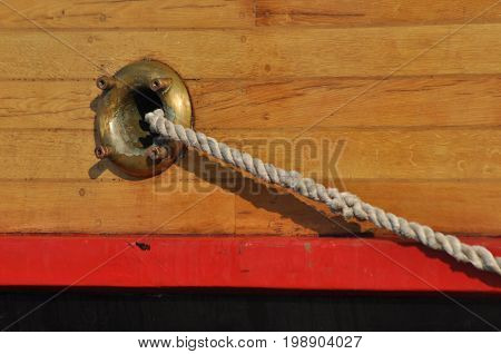 A mooring rope coming out of the hole in the side of the ship. Thick twisted rope.