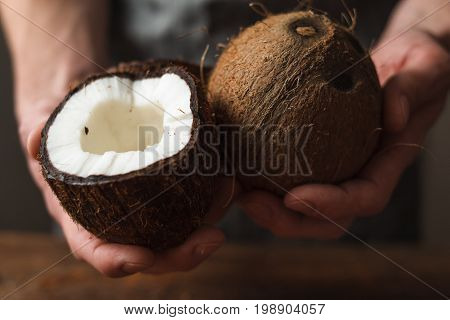 Coconuts holding in hands. Unrecognizable man or woman show you exotic nut with fresh white pulp