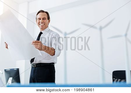 Content with results. Handsome pleasant man standing in the office and holding a big blueprint while looking at the wind turbine models standing on the table