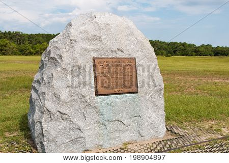 KILL DEVIL HILLS, NORTH CAROLINA - JULY 14, 2017:  Stone marker commemorating the location of the first successful flight by Wilbur and Orville Wright at the Wright Brothers National Memorial.