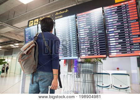 BANGKOK THAILAND - AUGUST 8 2017: Asian traveler man with backpack and carry on luggage suitcase looking at flight schedule in Suvarnabhumi Airport. Suvarnabhumi Airport is one of two international airports serving Bangkok.