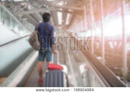 Blurred background airport interior with the passenger dragging luggage suitcase