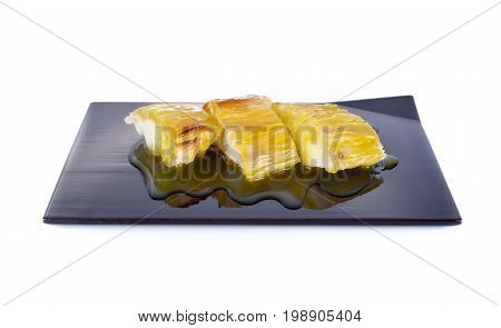 Thai dessert grilled cassava with coconut milk syrup on black plate and on white background