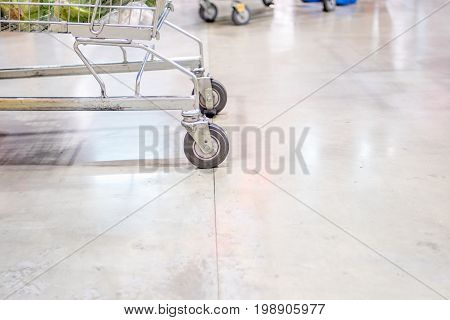 Close up shopping cart wheel at supermarket.