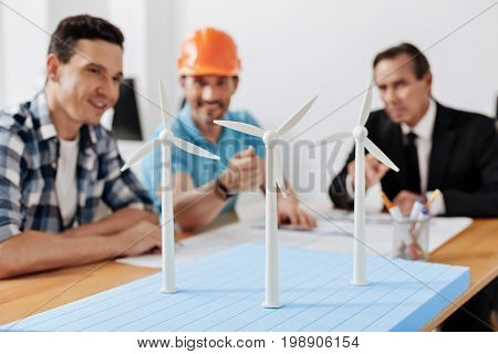 Important contribution. The focus being on a wind turbine model being pointed at by a young man in a hard hat surrounded by his colleagues during the discussion of a new wind power station project