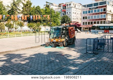Editorial image of street janitor using cleaning machine to sweep and clean sidewalk tile in Istanbul, Turkey on June 16, 2017.