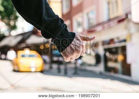 Image of urban hitchiker trying to catch yellow taxi cab in the city setting.