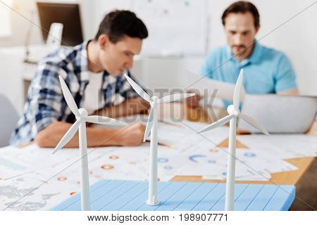 Engaged in work. The focus being on the wind turbine models standing on the office full of printouts being studied by two busy men