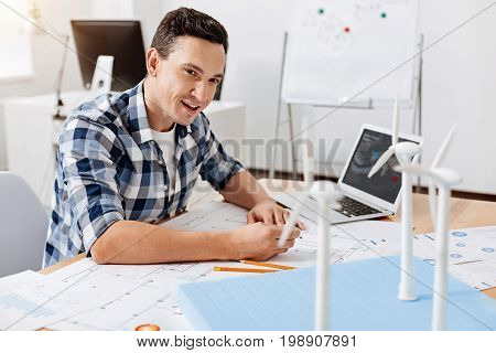 Necessary adjustments. Charming young architect sitting at the table and making some changes in his blueprint according to the peculiarities of wind turbine construction