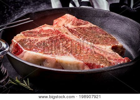 Fresh raw meat t-bone steak in a skillet marinated with herbs and spices shot with a dark background.