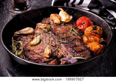 Pan grilled large t-bone steak with garlic tomatoes herbs and seasoning.