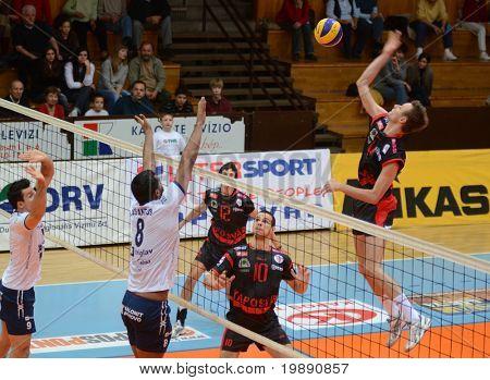 KAPOSVAR, HUNGARY - NOVEMBER 19: Krisztian Csoma (R) strikes the ball at a Middle European League volleyball game Kaposvar (HUN) vs Salonit Anhovo (SLO), November 19, 2010 in Kaposvar, Hungary