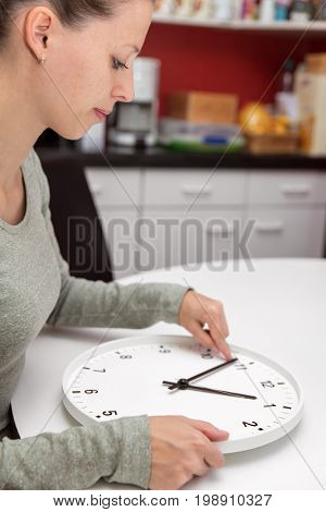 A Woman Changes The Time On A Clock
