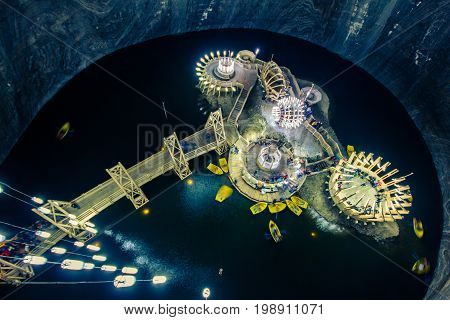 Pavilions on an artificial island in the salt lake, underground. Boat, wooden structures, the bridge leading to the island, the original rounded design and architecture. Salt mine - Solina Turda, Romania.
