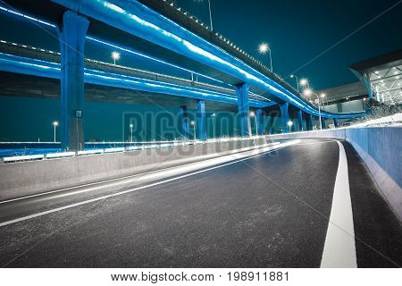 Empty Road Floor With City Viaduct Bridge Of Neon Lights Night
