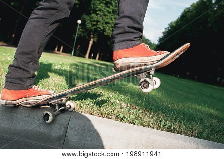 Skateboarder make back slide trick on the park. Practice of holding skate balance. Lifestyle Workout Leisure Fun Concept