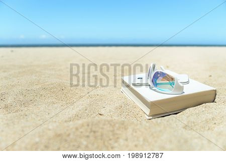 Close up of white sunglasses, book and phone on the beach on warm yellow sand, with blue ocean and sky on background